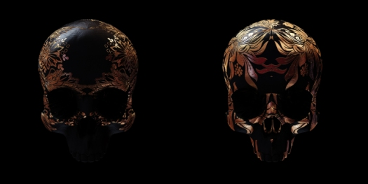 Image of 2 skulls made of copper, with flower designs etched into them.