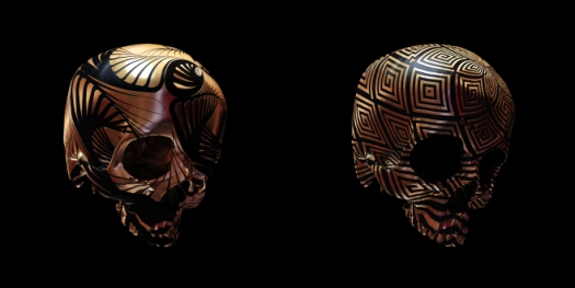 Image of two copper skulls with geometric designs etched into them