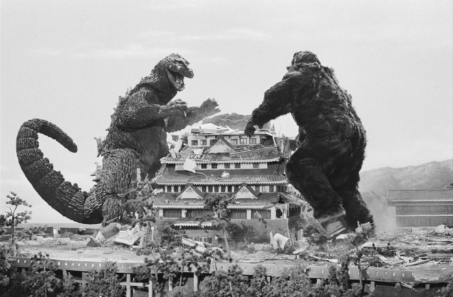 giant lizard fighting giant gorilla over a japanese castle
